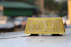 Taxiljustecknet eller taxitecknet i gråbrun gul färg med skalar text på biltaket royaltyfri fotografi