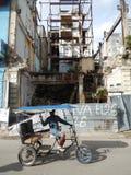 TAXIRICKSHAWEN OCH FÖRDÄRVAR AV EN BYGGNAD, HAVANNACIGARREN, KUBA Royaltyfri Fotografi