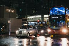 Taxis and buses in Canary Wharf, London, UK, on a rainy winter evening stock image