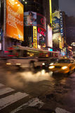 Taxis and buses pass by on busy street at Times Square, Manhattan Stock Photo