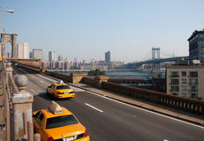 Taxis croisant la passerelle de Brooklyn Photos stock