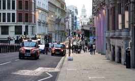Taxis and Cyclist on a London Street Royalty Free Stock Photo