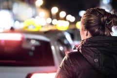 Taxis dans la rue de ville la nuit Femme recherchant un tour de cabine photo stock