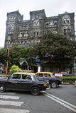 Taxis drive on a street in Mumbai Royalty Free Stock Images