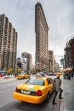 Taxis in einer Straße mit dem Plätteisengebäude im Hintergrund Stockfotografie