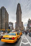 Taxis in einer Straße mit dem Plätteisengebäude im Hintergrund Lizenzfreie Stockfotos