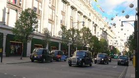 Taxis en voetgangers buiten Selfridges, de straat van Oxford, Londen, Engeland stock video