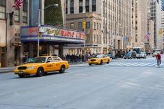 Taxis jaunes et trafic devant le théâtre de variétés par radio de ville Image libre de droits