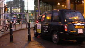 Taxis at Manchester Piccadilly station. MANCHESTER, ENGLAND, UK - FEBRUARY, 2017: British symbol black cabs, hackney carriages or taxis entering through security stock video