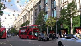 Taxis and red double decker London buses driving past Selfridges, Oxford street, London, England stock video