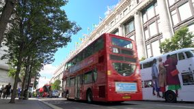 Taxis and red double decker London buses driving past Selfridges, Oxford Street, London, England stock video footage