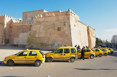 Taxis wait for passengers in from of the medina wall in Sfax, Tunisia. Stock Photos