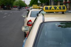 Taxis waiting in line. A row of three taxis waiting in line for customers on Berlin's Unter den Linden, TAXI sign big in right area of the frame, on a grey day Royalty Free Stock Photos