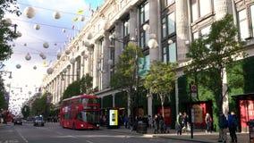 Taxisbussen en voetgangers buiten Selfridges, de straat van Oxford, Londen, Engeland stock footage