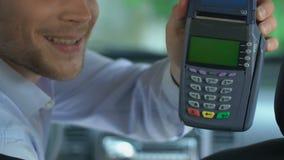 Taxista que da el terminal al cliente, transferencia cashless fácil, servicios del pago almacen de metraje de vídeo