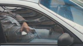 Taxista que descansa em seu carro estacionado ao verificar seu telefone celular à disposição A maioria de ordens são recebidas do filme