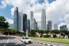 Taxitaxi som kör i väg i det Singapore centret med Singapore skyskrapor som bygger i bakgrund askfat royaltyfria foton