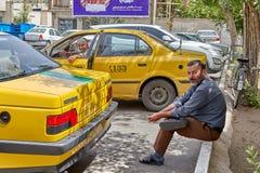 Taxitreiber steht im Parkplatz Taxis, Kashan, der Iran still Lizenzfreie Stockfotografie