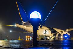 Taxiway, side row lights on the background of a large passenger aircraft at the night airport apron. Taxiway, side row lights on the background of a large royalty free stock photos