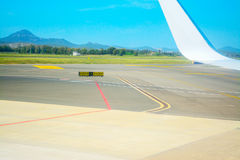 Taxiway signs and airplane wing Stock Image