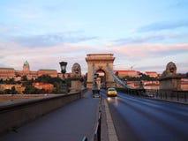 Taxy på den Budapest bron på morgonen arkivbilder