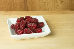 Tayberries on plate on wooden table Stock Photos
