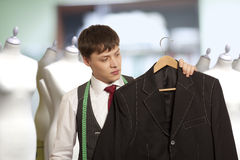 Taylor holds a mans suit Royalty Free Stock Photo