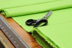 Taylor shop. Scissors and roll of textile on cutting table Stock Photos