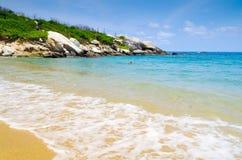 TAYRONA,哥伦比亚2017年10月20日:在美丽的白色沙子、大海和华美的天空的未认出的妇女游泳 库存图片