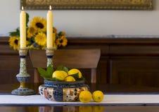 Tazón de fuente antiguo, palmatorias, limones Fotografía de archivo