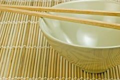 Tazón de fuente de arroz en la estera de bambú con los palillos Fotografía de archivo libre de regalías