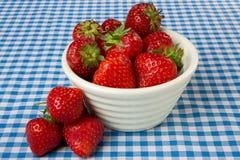 Tazón de fuente de fresas en un mantel azul de la guinga Imagen de archivo libre de regalías
