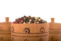 Tazón de fuente de madera por completo de pimientas mezcladas Imágenes de archivo libres de regalías