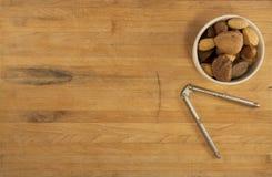 Tazón de fuente de tuercas mezcladas con el cascanueces Imagen de archivo