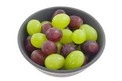 Tazón de fuente de uvas rojas y verdes Imagen de archivo libre de regalías