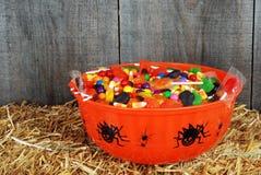 Tazón de fuente del caramelo de víspera de Todos los Santos en la paja Fotos de archivo