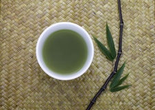 tazón de fuente del té verde con las hojas de bambú Fotos de archivo libres de regalías