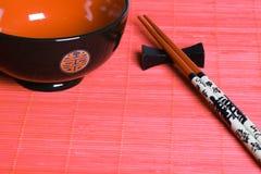 Tazón de fuente y palillos japoneses. Imagen de archivo