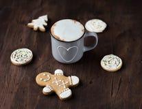 Taza acogedora de cacao con el pan de jengibre de la Navidad en una tabla de madera imagen de archivo libre de regalías