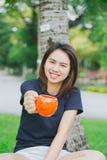 Taza adolescente asiática de la sonrisa de la manija en el parque verde Imagenes de archivo