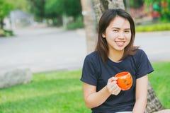 Taza adolescente asiática de la sonrisa de la manija en el parque verde Foto de archivo libre de regalías