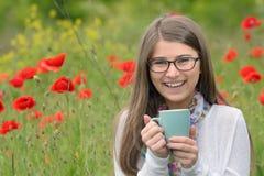 Taza adolescente de la bebida de la muchacha de té Fotografía de archivo libre de regalías