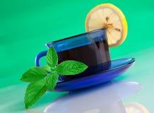 Taza agradable de té y de menta en fondo verde Imagen de archivo libre de regalías