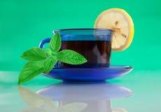 Taza agradable de té y de menta en fondo verde Imagen de archivo