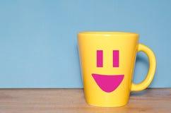 Taza amarilla con la cara feliz Foto de archivo libre de regalías