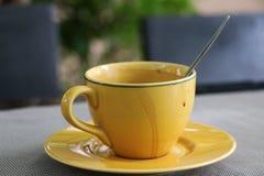 Taza amarilla de bebida caliente Imagen de archivo libre de regalías