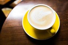 Taza amarilla de caf? arom?tico en una tabla de madera imagen de archivo