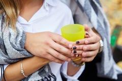 Taza amarilla de té caliente en las manos del amante Pares jovenes imagen de archivo
