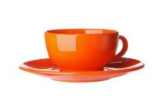 Taza anaranjada aislada en blanco Foto de archivo libre de regalías