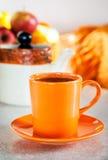 Taza anaranjada colorida de té negro Fotografía de archivo